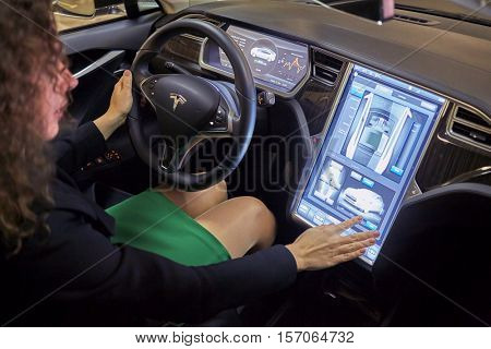 MOSCOW, RUSSIA - NOV 11, 2015: Smiling woman (with model release) sits in the Tesla S car. The Model S 17 inch touchscreen controls most of the car functions.