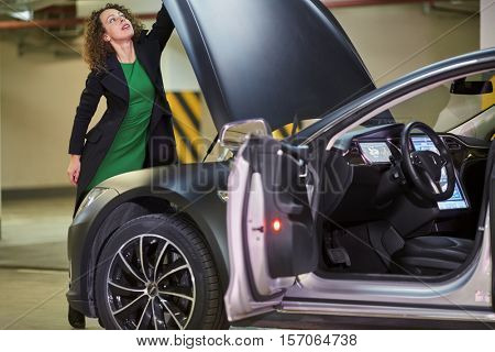 MOSCOW, RUSSIA - NOV 11, 2015: Young woman (with model release) opens hood of the Tesla S car. The Tesla Model S produced by Tesla Motors, and introduced in June 2012.