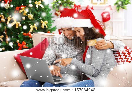 Young couple shopping online with credit card at home for Christmas. Snowy effect. Christmas shopping concept.