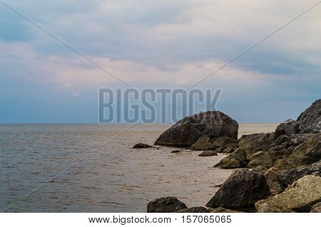 Evening sky calm sea with a pinkish tinge and rocks on the shore