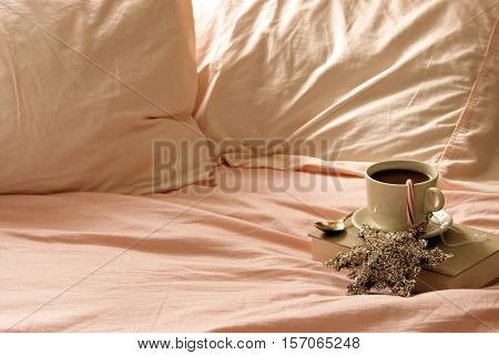 Rumpled bedsheets open to coffee cup and saucer on vintage book. Room for copy. Christmas holiday décor items