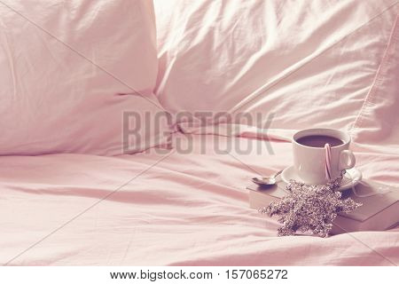 Rumpled bedsheets open to coffee cup and saucer on vintage book. Room for copy. Christmas holiday décor items.