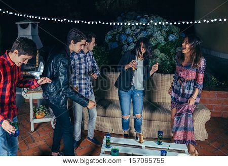 Happy young friends dancing and having fun in a outdoors party. Friendship and celebrations concept.