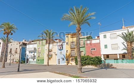 Row of pastel colored terrace style traditional Mediterranean homes with palm tree La Vila Joisa, Alicante Spain