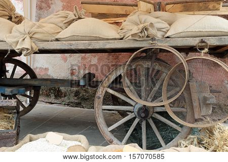 antique wagon with wooden wheels and the jute sacks over