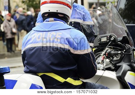a french policeman motorcyclist guarding the city