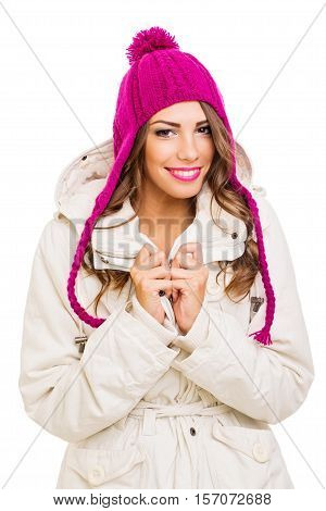 Beautiful young woman in winter jacket and knitted hat. Closeup studio portrait of gorgeous teenage girl in beige cozy jacket and handmade pink beanie. Isolated on white background, medium retouch.