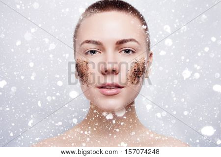 Smiling woman with short hair bald cleans the skin coffee skrub studio shot close-up portrait. beauty people advertisement winter and health concept . over snow on gray background