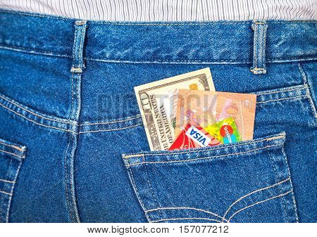 SAMARA RUSSIA - NOVEMBER 11 2016: Ten american dollars ten euro notes and credit cards sticking out of the blue jeans pocket