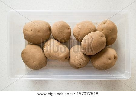 Raw potatoes in a plastic container on flor.