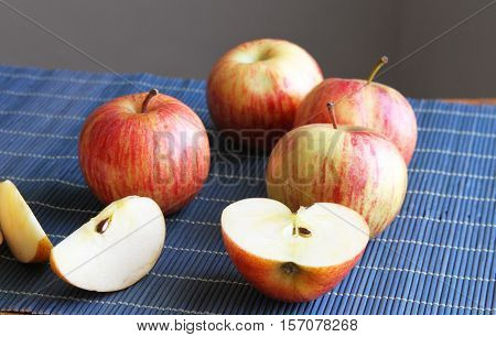 Gala red apples whole half and sliced on a place mat