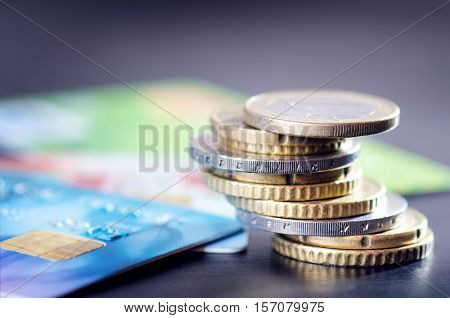 Euro money and credit cards are isolated on a dark background. Currency of Europe. Balance of money. Building from coins.