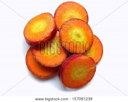 Slices of several red carrot on white