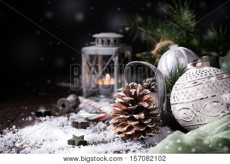 Christmas composition with pine cone, candle, christmas ball and decoration on black background with snow. Christmas greeting card. Copy space.