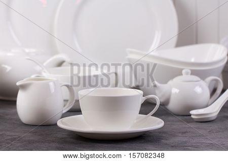 Set of white dishes on grey concrete background