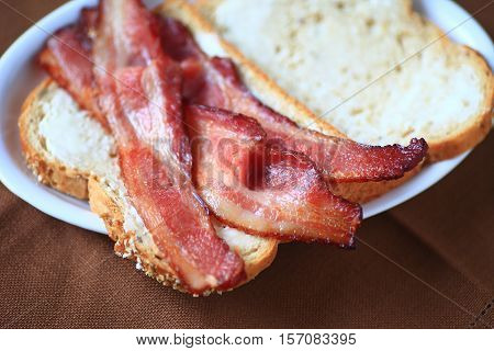 Bacon slices on buttered whole-grain bread closeup