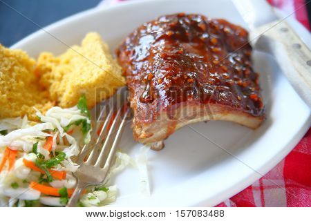 Garlic barbecue sauce on baby back ribs with cornbread and coleslaw on white platter