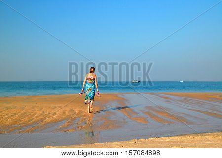 GOA INDIA - NOVEMBER 23 2007: Caucasian woman walks on the beach