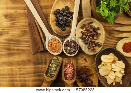 Various kinds of spices on the kitchen table. Seasoning food. Sales of exotic spices. Advertising on spices. Powder spices on spoons in wooden table background.