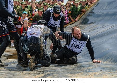 Tyumen, Russia - June 11, 2016: Race of Heroes project on the ground of the highest military and engineering school. Members of team give first aid to companion after unsuccessful attempt at stage