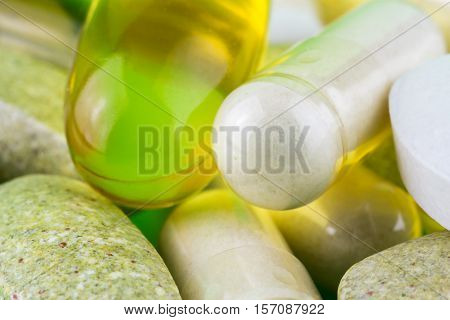 Mixed natural food supplement pills omega 3 multivitamin and glucosamine capsules macro image