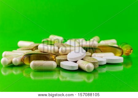Mixed natural food supplement pills omega 3 calcium multivitamin and glucosamine capsules on green background