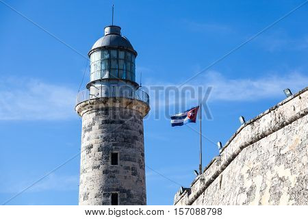 Lighthouse at Castillo del Morro, El Morro Fort in Havana with a waving Cuban flag on a clear day