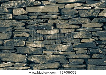 Natural stonewall texture for background. Stone wall built from stones and rocks of different sizes.