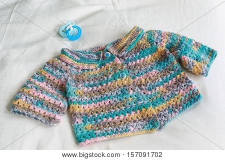 Handmade crocheted baby sweater with soother.