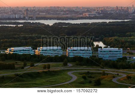 Business center with high buidlings, river and green forest in Moscow, Russia at summer evening