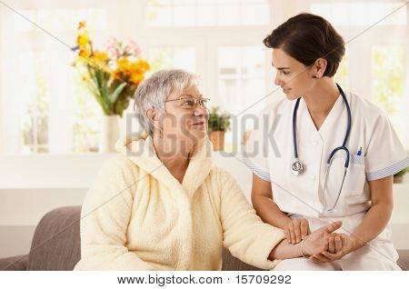 Nurse measuring heartbeat of senior woman at home. Looking at camera, smiling.?