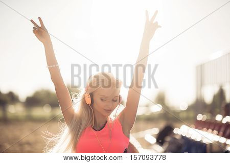 Young woman in sport wear enjoys and smiles listening music with orange earphones. She puts her hands up enjoying her life
