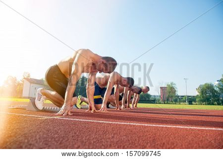 Male athletics runners on starting line without shirts. long-distance runner, dynamic image, closeup of photo