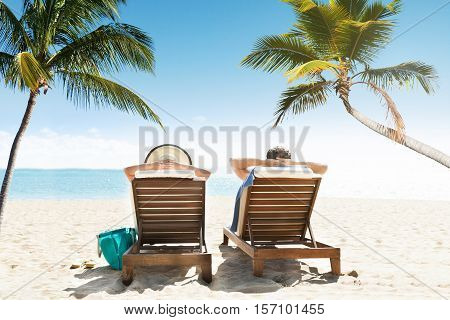 Rear View Of Couple Relaxing On Lounge Enjoying Vacation On Beach