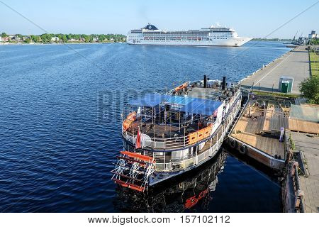 Ocean Cruise Ship MSC Opera turning round on Daugava river and Touristic river boat Pearl of Riga - Rigas perle - with paddle wheel by the Riga city embankement, Latvia