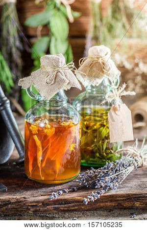 Therapeutic Tincture With Herbs And Alcohol On Old Wooden Table
