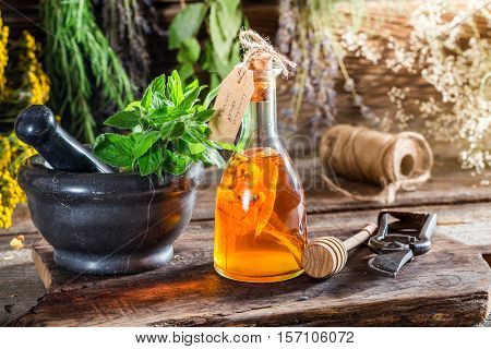 Aromatic Tincture With Herbs And Alcohol On Old Wooden Table