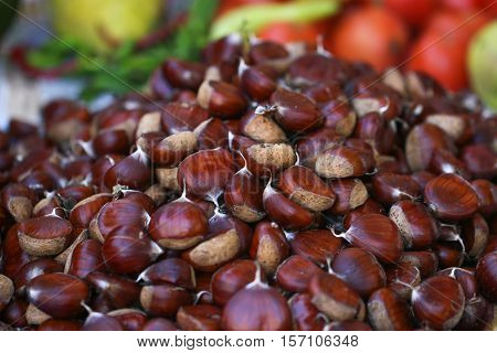 Many ripe chestnuts. Brown chestnuts as background.