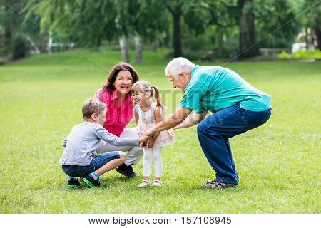Happy Old Grandparents Having Fun With Grandchildren In Park