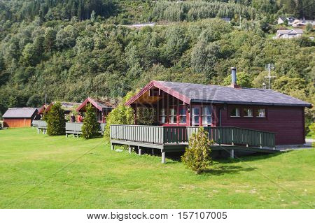 Beautiful landscape with classical scandinavian camping cottage wooden house cabin chalet hut, on a lake shore coastline, in sunny summer day in Norway