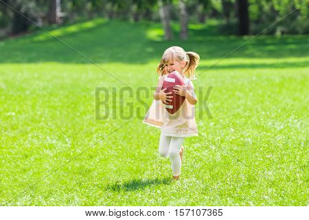 Little Happy Girl Holding Ball While Playing American Football In The Park