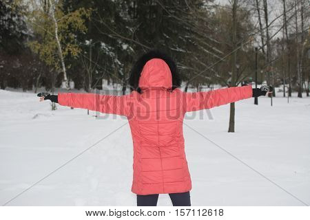 Girl standing arms to the side in the winter. With his back to the camera