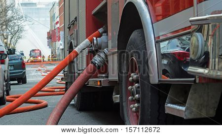 Fire truck hose urban city street with burning building in background water flowing several stories high team of many firemen fighting fire selective focus on fire truck and gear