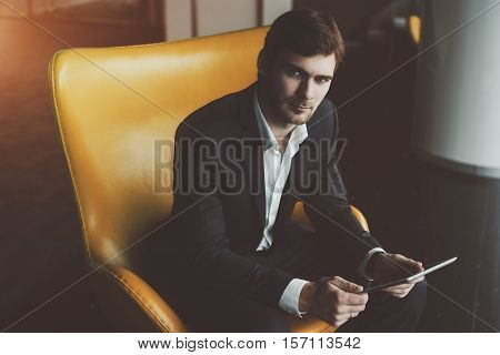 Young serious successful man entrepreneur in formal business suite with a beard sitting on yellow armchair with digital tablet in office interior preparing to business meeting