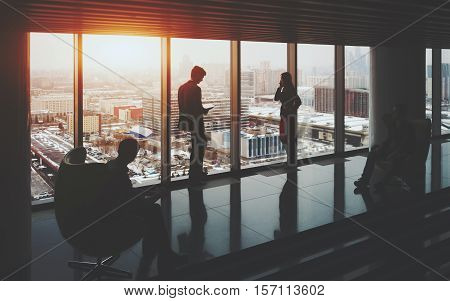 Businessman and businesswoman standing near window of skyscraper two their male colleagues sitting on armchairs on opposite sides winter cityscape outside office interior with reflections