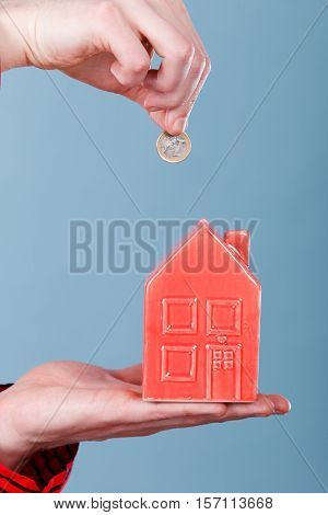 Savings for future plans. Male hands with red little house piggy bank and silver coin. Money loin for family home better life.