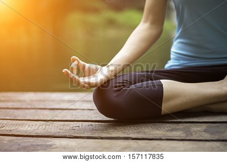 Close up hand. Woman do yoda outdoor. Woman exercising yoga at the nature background select focus