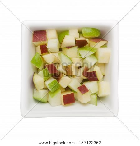 Diced green and red apple in a square bowl isolated on white background