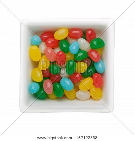 Colorful jelly bean candies in a square bowl isolated on white background