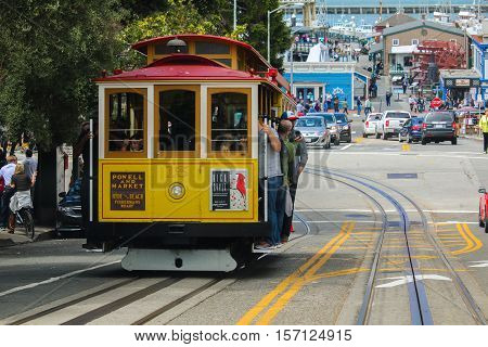 San Francisco California - Mai 23 2015: Tourists riding on the iconic cable car blue sky day at top of Hyde Street view overlooking the bay water and Alcatraz prison